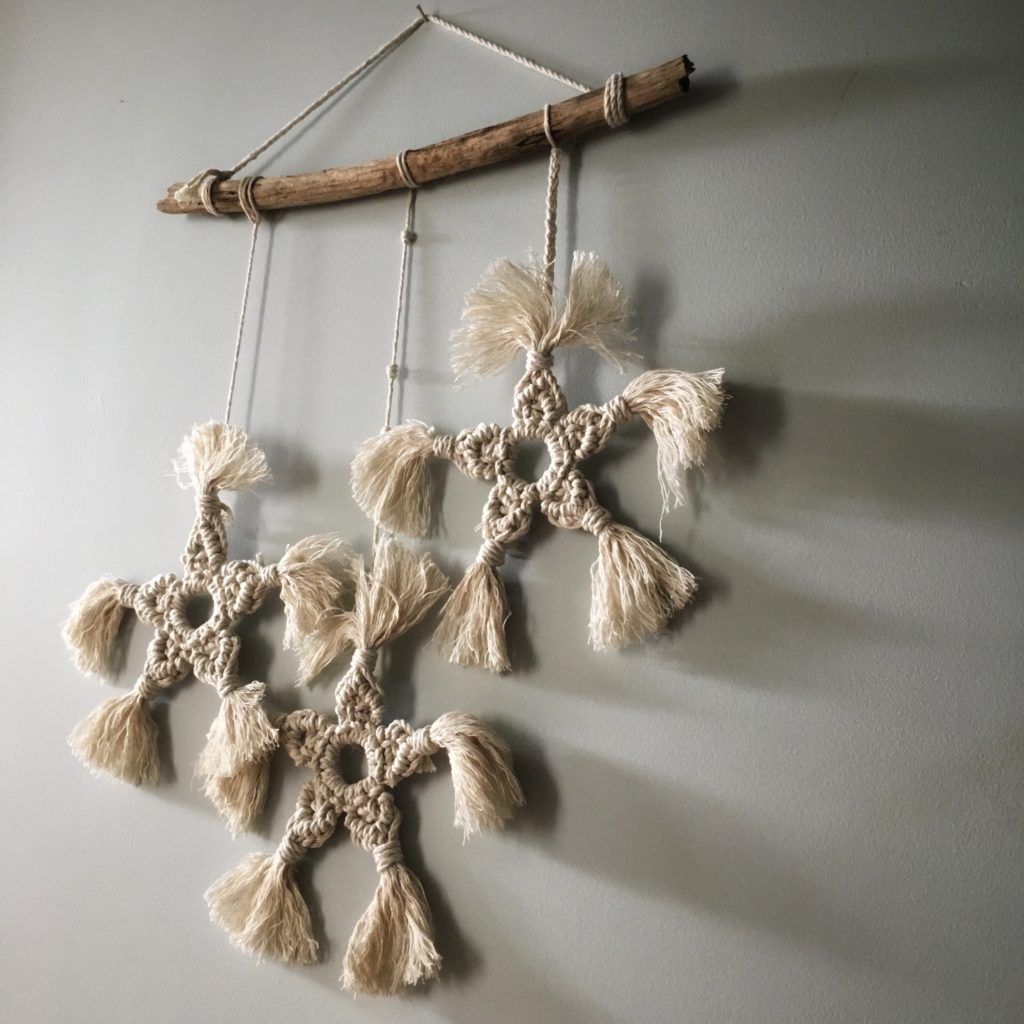 Three macrame stars made with natural cotton rope and strung along a piece of driftwood.